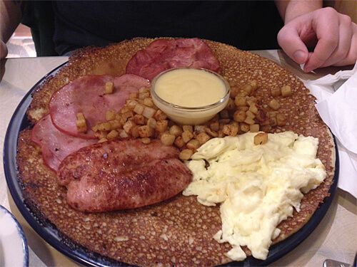 The Boar's (Farmer's) Pannekoek - two eggs, bratwurst, slices of DeBakon and Ham, served with hash browns and Hollandaise Sauce on top of a Dutch Pannekoek.