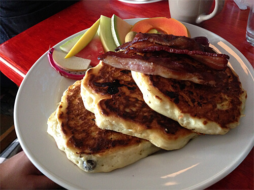 Blueberry Yogurt Pancakes - big, light, fluffy blueberry pancakes with butter, maple syrup, fresh fruit and bacon. ($15)