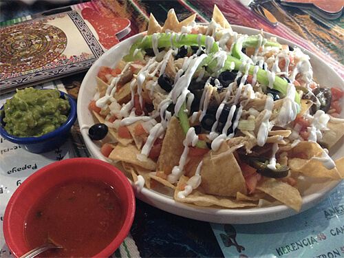 Amigos Nachos - freshly made crispy tortilla chips covered with mozza, tomatoes, onions, jalapenos, olives & peppers, with sour cream and salsa. $12.99