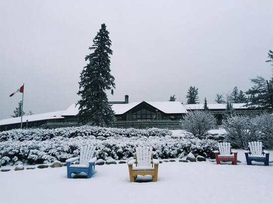 The Fairmont Jasper Park Lodge's iconic beach chairs draped in snow.
